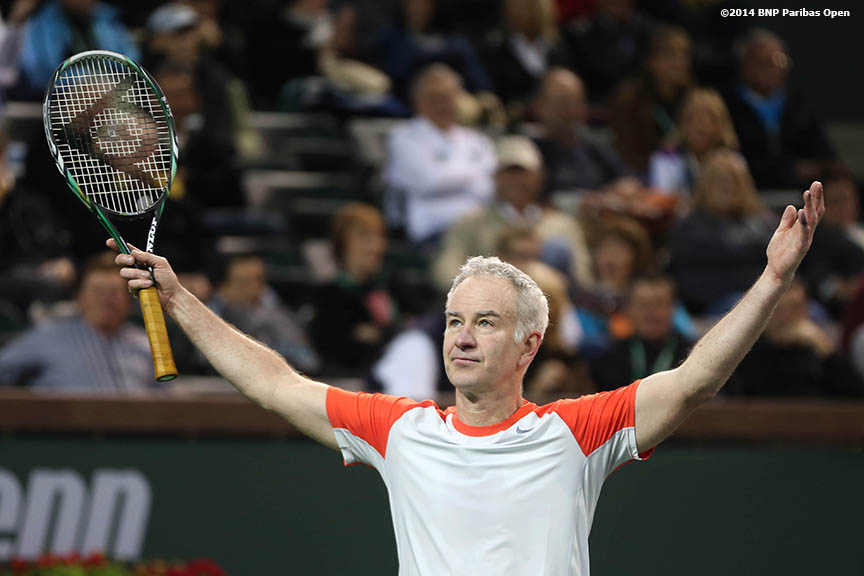 """John McEnroe reacts after winning a point during the McEnroe Challenge for Charity presented by Esurance Saturday,  March 1, 2014 in Indian Wells, California."""