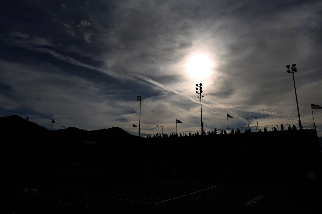 """Fans watch a match as the sun sets over the Indian Wells Tennis Garden in Indian Wells, California Wednesday, March 5, 2014."""