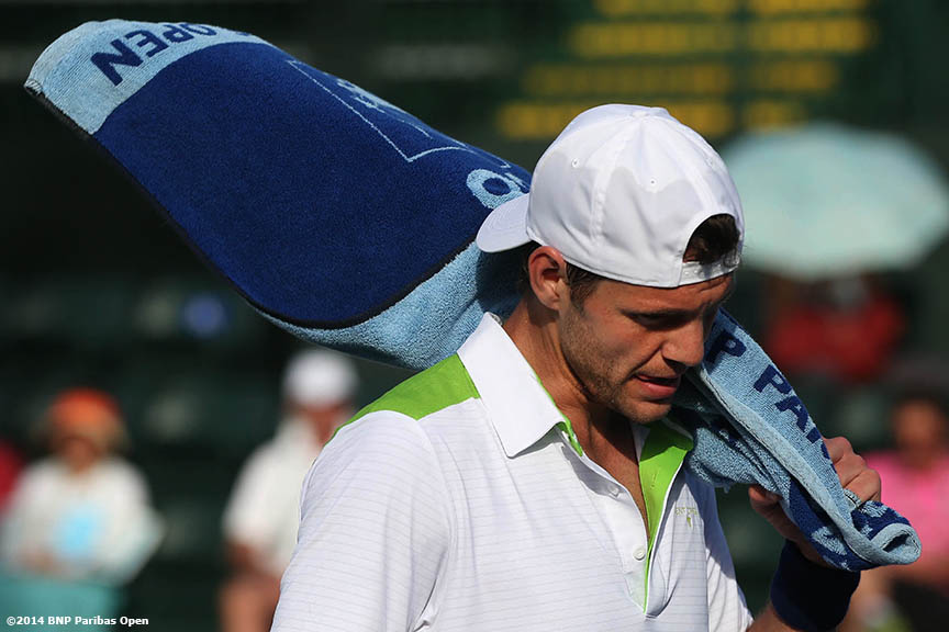 """Paul Henri Mathieu picks up his towel during a match against  James Ward in Indian Wells, California Wednesday, March 5, 2014."""