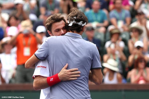 """Roger Federer and Stan Wawrinka hug after defeating Rohan Bopanna and Aisam-Ul-Haq Qureshi in a first round doubles match at the 2014 BNP Paribas Open in Indian Wells, California Friday, March 7, 2014."""