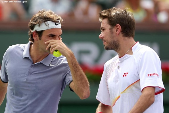 """Roger Federer and Stan Wawrinka chat during a first round doubles match against Rohan Bopanna and Aisam-Ul-Haq Qureshi at the 2014 BNP Paribas Open in Indian Wells, California Friday, March 7, 2014."""