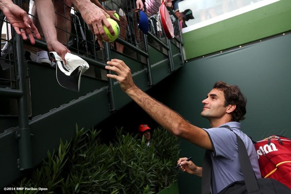 """Roger Federer signs autographs after winning a first round doubles match against Rohan Bopanna and Aisam-Ul-Haq Qureshi at the 2014 BNP Paribas Open in Indian Wells, California Friday, March 7, 2014."""