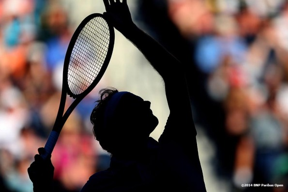 """Roger Federer serves during a match against Paul Henri Mathieu in the second round of the 2014 BNP Paribas Open Saturday, March 8, 2014 in Indian Wells, California."""