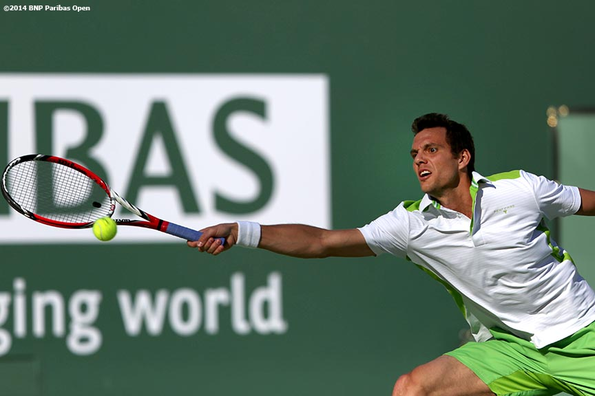 """Paul Henri Mathieu hits a forehand against Roger Federer at the BNP Paribas Open Saturday, March 8, 2014 in Indian Wells, California."""