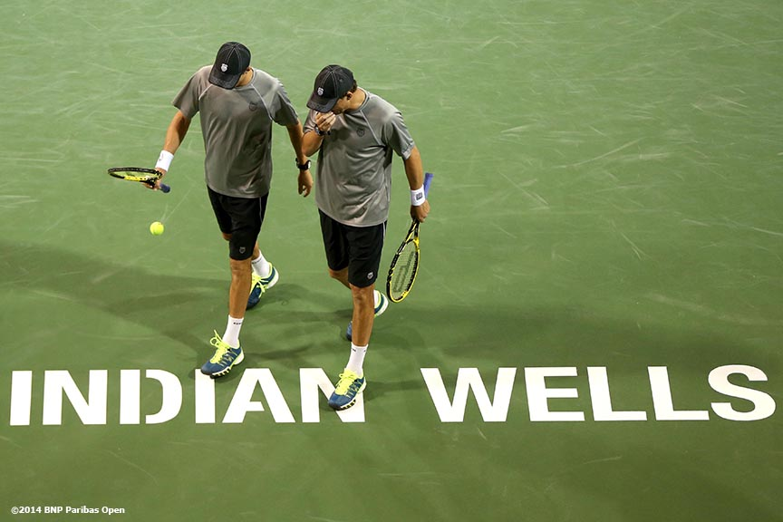 """Bob and Mike Bryan chat between points during a match against Scott Lipsky and Florian Mayer at the 2014 BNP Paribas Open Saturday, March 8, 2014 in Indian Wells, California."""