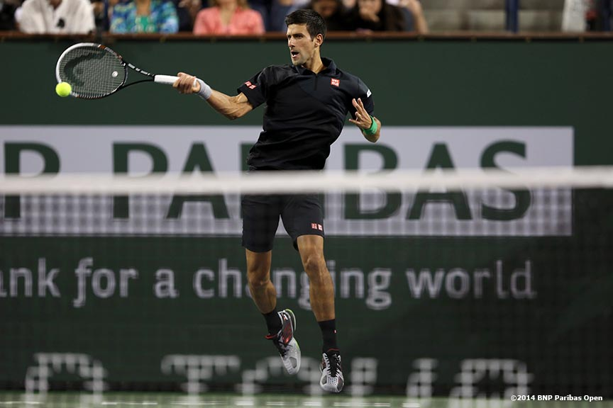 """Novak Djokovic hits a forehand against Victor Hanescu in a second round match at the 2014 BNP Paribas Open in Indian Wells, California Sunday, March 9, 2014."""