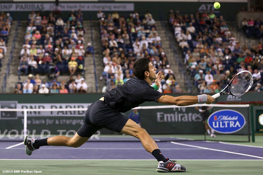 """Novak Djokovic reaches for a return from Victor Hanescu in a second round match at the 2014 BNP Paribas Open in Indian Wells, California Sunday, March 9, 2014."""