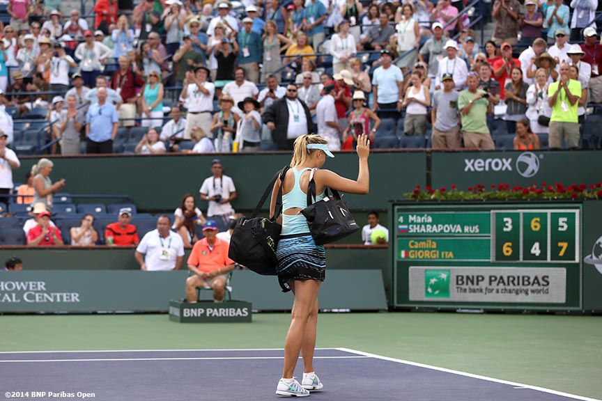 """""""Maria Sharapova waves to the crowd as she walks off court after being defeated in three sets by Camila Giorgi in the third round of the BNP Paribas Open Monday, March 10, 2014 in Indian Wells, California."""""""