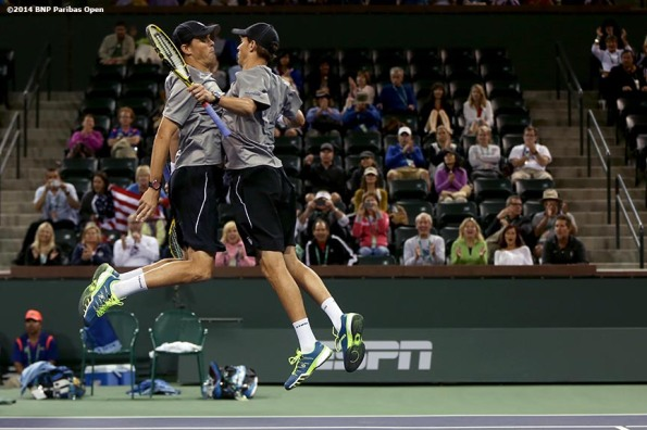 """Bob and Mike Bryan chest bump each other after winning their third round doubles match Tuesday, March 11, 2014 in Indian Wells, California."""