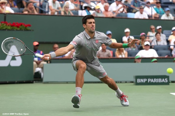 """Novak Djokovic lunges for a forehand against Alejandro Gonzalez in a third round match at the 2014 BNP Paribas Open Tuesday, March 11, 2014 in Indian Wells, California."""