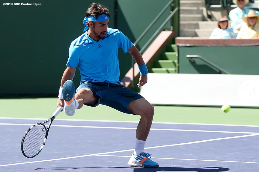 """Fabio Fognini hits a shot beween his legs during a fourth round match against Alexandr Dolgopolov at the 2014 BNP Paribas Open Wednesday, March 12, 2014 in Indian Wells, California."""