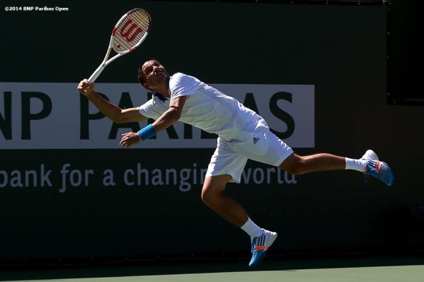 """Alexandr Dolgopolov jumps as he returns a shot from Fabio Fognini in a fourth round match at the 2014 BNP Paribas Open Wednesday, March 12, 2014 in Indian Wells, California."""