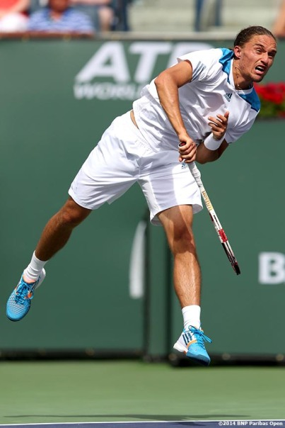 """Alexandr Dolgopolov serves to Milos Raonic in the quarterfinal of the 2014 BNP Paribas Open Thursday, March 13, 2014 in Indian Wells, California."""
