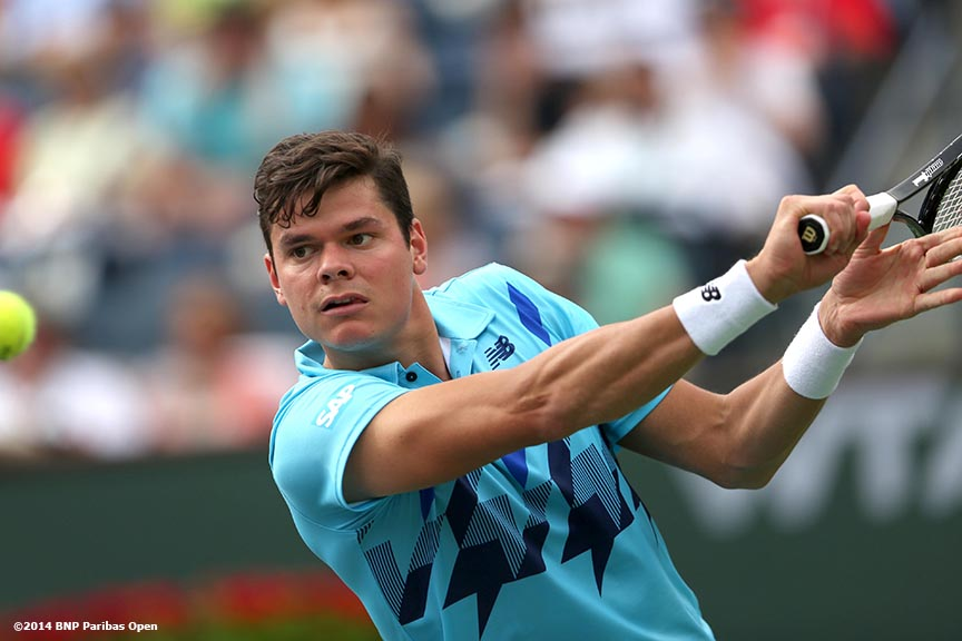 """Milos Raonic hits a backhand against Alexandr Dolgopolov in the quarterfinal of the 2014 BNP Paribas Open Thursday, March 13, 2014 in Indian Wells, California."""
