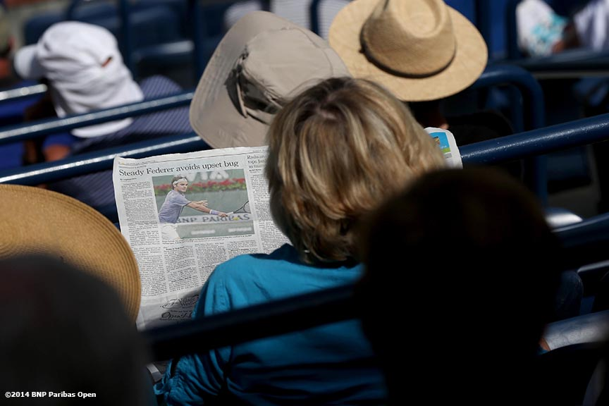 """A fan reads the newspaper during a match between Dominica Cibulkova and Li Na Thursday, March 13, 2014 in Indian Wells, California."""