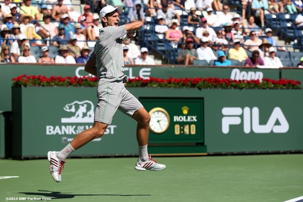 """Novak Djokovic hits a forehand against Julien Benneteau in the quarterfinal of the 2014 BNP Paribas Open Friday, March 14, 2014 in Indian Wells, California."""