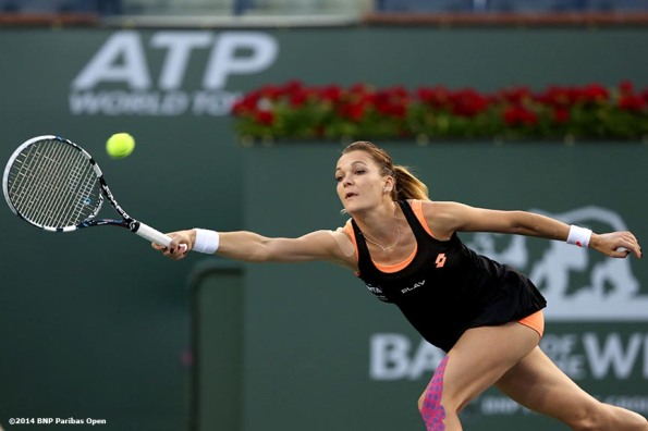 """Agnieszka Radwanska hits a forehand against Simona Halep in the semifinal of the 2014 BNP Paribas Open Friday, March 14, 2014 in Indian Wells, California."""