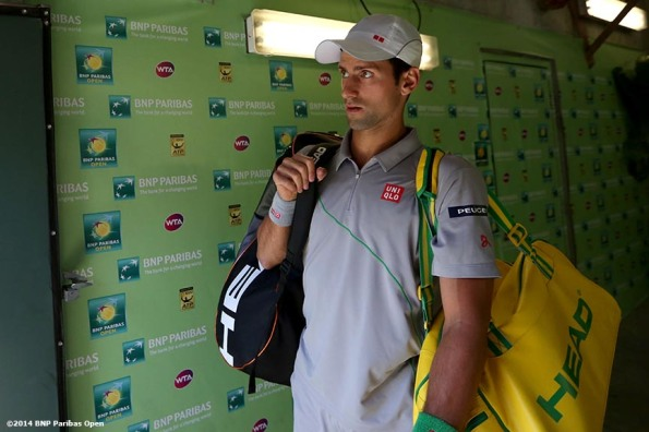 """Novak Djokovic waits to be introduced before playing John Isner in the semifinals of the 2014 BNP Paribas Open Saturday, March 15, 2014 in Indian Wells, California."""