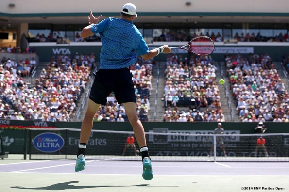 """John Isner hits a forehand against Novak Djokovic in the semifinals of the 2014 BNP Paribas Open Saturday, March 15, 2014 in Indian Wells, California."""