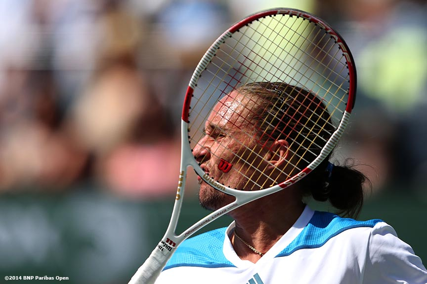 """Alexandr Dolgopolov hits a forehand against Roger Federer in the semifinals of the 2014 BNP Paribas Open Saturday, March 15, 2014 in Indian Wells, California."""