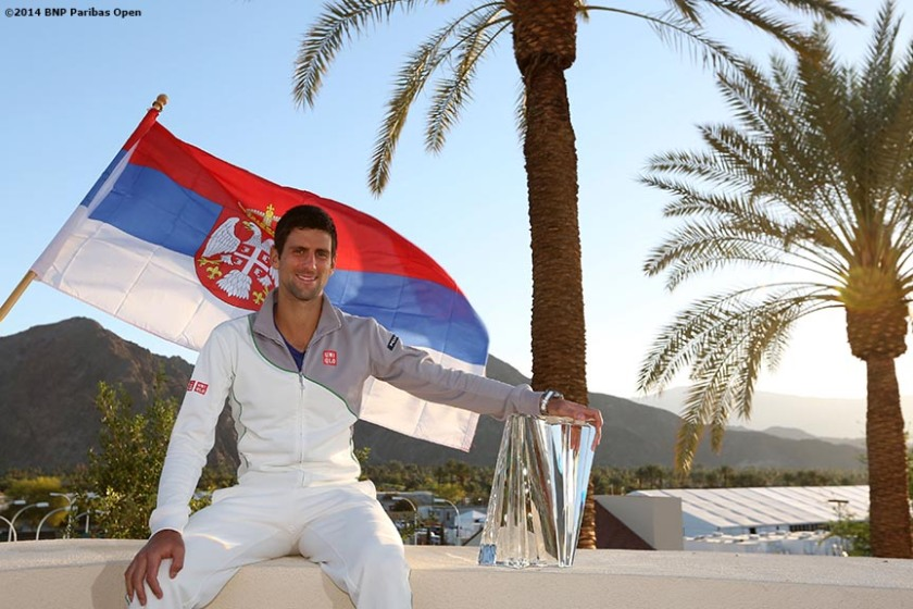 """""""Novak Djokovic poses with the trophy and the Serbian flag after defeating Roger Federer to win the 2014 BNP Paribas Open men's singles championship Sunday, March 16, 2014 in Indian Wells, California."""""""