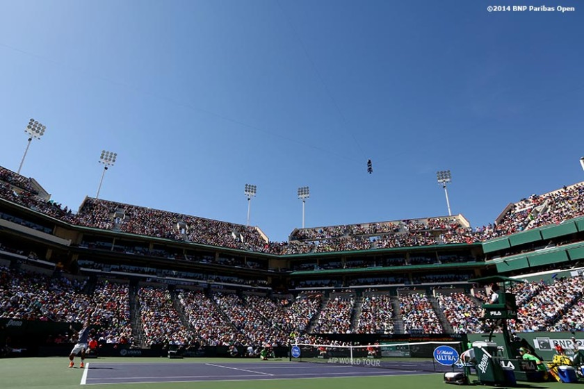 """Roger Federer serves to Novak Djokovic during the 2014 BNP Paribas Open men's finals Sunday, March 16, 2014 in Indian Wells, California."""
