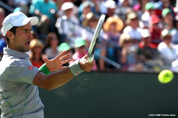 """Novak Djokovic hits a forehand during the 2014 BNP Paribas Open against Roger Federer Sunday, March 16, 2014 in Indian Wells, California."""
