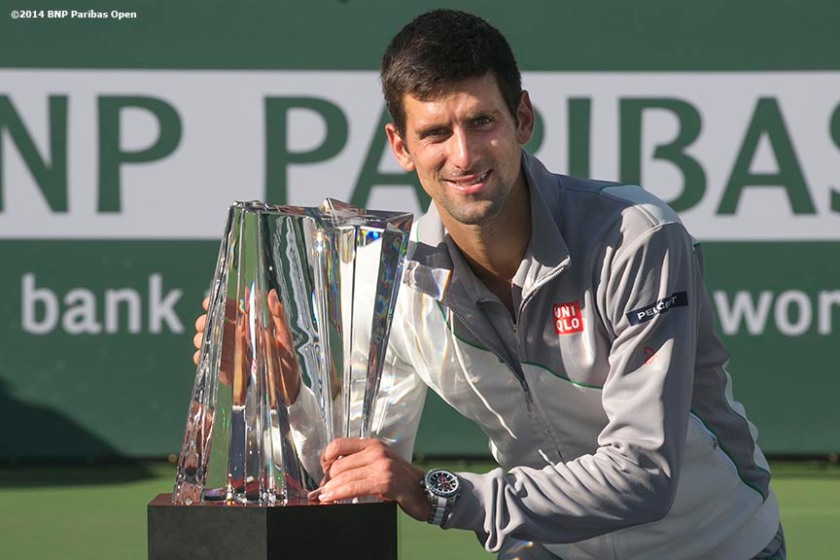 """Novak Djokovic poses with the trophy after defeating Roger Federer to win the 2014 BNP Paribas Open men's singles championship Sunday, March 16, 2014 in Indian Wells, California."""