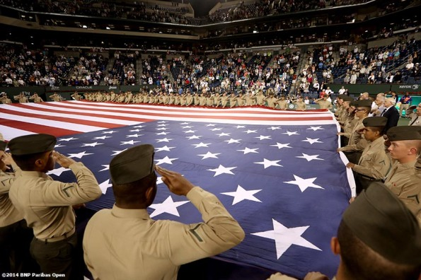 """Military members hold an American Flag during a 'Salute To Heroes' ceremony at the Indian Wells Tennis Garden in Indian Wells, California Friday, March 7, 2014."""