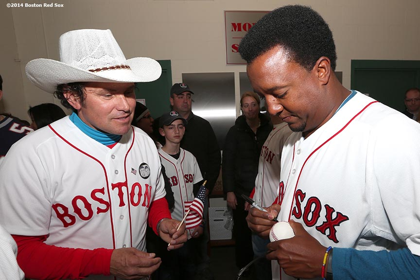 """Boston Marathon hero Carlos Arredondo gets an autograph from former Boston Red Sox pitcher Pedro Martinez during a meet and greet before the Boston Red Sox 2014 home opening day and World Series ring ceremony Friday, April 4, 2014 at Fenway Park in Boston, Massachusetts."""