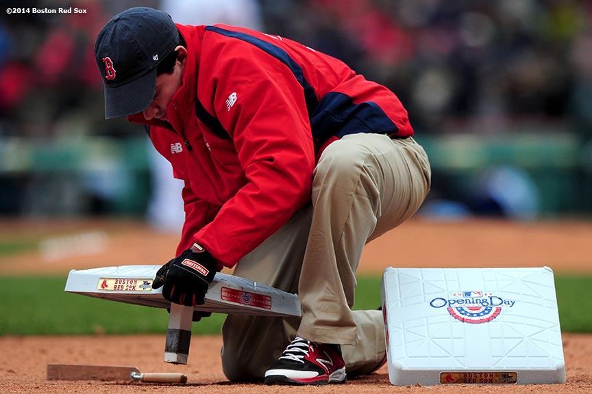 """A grounds crew member changes bases during the Boston Red Sox 2014 home opener Friday, April 4, 2014 at Fenway Park in Boston, Massachusetts."""