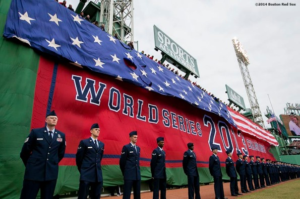"""Members of the Hanscom Air Force Base assist in a flag drop of the American flag during the Boston Red Sox World Series ring ceremony at the 2014 season home opener Friday, April 4, 2014 at Fenway Park in Boston, Massachusetts."""