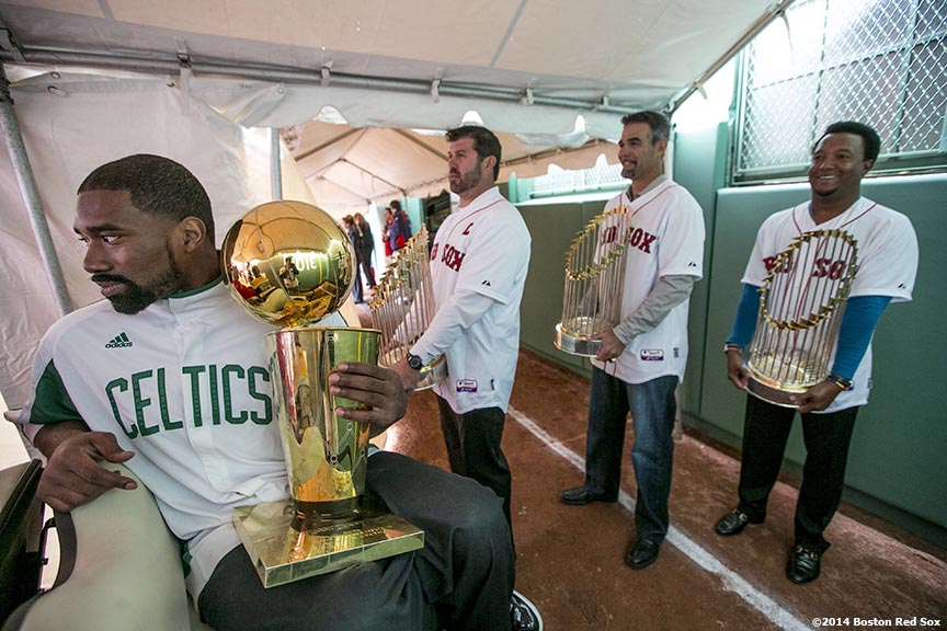 """Former Boston Celtics player Leon Powe and former Boston Red Sox players Jason Varitek, Mike Lowell, and Pedro Martinez hold championship trophies before they are introduced during the Boston Red Sox World Series ring ceremony at the 2014 season home opener Friday, April 4, 2014 at Fenway Park in Boston, Massachusetts."""