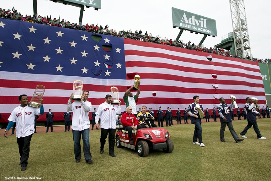 """(From left to right) Former Boston Red Sox players Pedro Martinez, Mike Lowell and Jason Varitek, former Mayor of Boston Tom Menino, former Boston Celtics player Leon Powe, former Boston Bruins player Mark Recchi, and former New England Patriots players Tedy Bruschi, Troy Brown, and Ty Law display championship trophies as they are introduced during the Boston Red Sox World Series ring ceremony at the 2014 season home opener Friday, April 4, 2014 at Fenway Park in Boston, Massachusetts."""