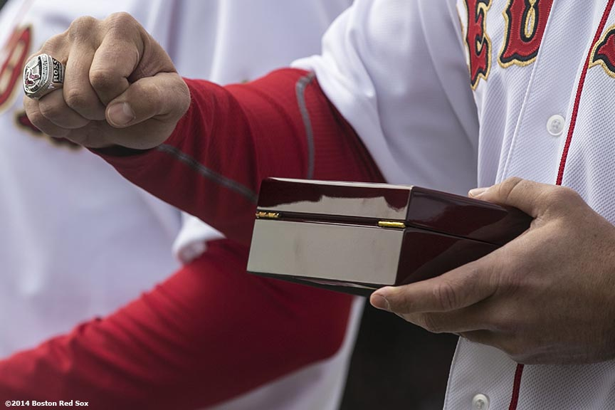 """Boston Red Sox catcher David Ross puts on his ring during the World Series ring ceremony at the 2014 season home opener Friday, April 4, 2014 at Fenway Park in Boston, Massachusetts."""