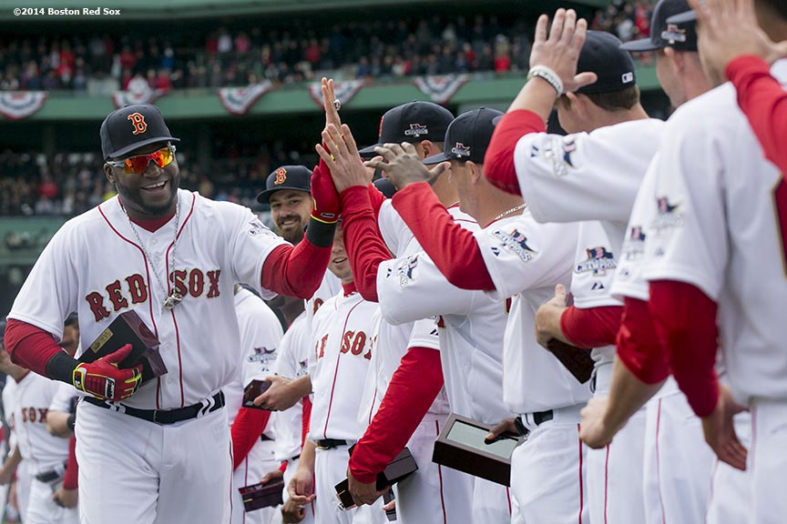 """Boston Red Sox designated hitter David Ortiz high fives teammates during the World Series ring ceremony at the 2014 season home opener Friday, April 4, 2014 at Fenway Park in Boston, Massachusetts."""