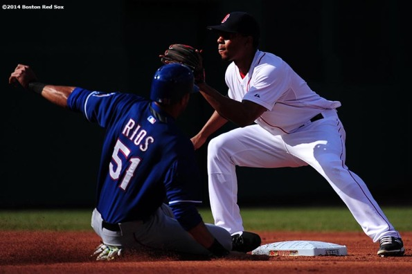 """Boston Red Sox shortstop Xander Bogaerts applies a tag to right fielder Alex Rios during the first inning of a game against the Texas Rangers at Fenway Park in Boston, Massachusetts Wednesday, April 9, 2014."""