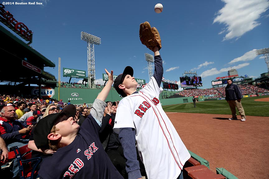 """Young fans reach for a baseball during a game between the Boston Red Sox and the Baltimore Orioles Saturday, April 19, 2014 at Fenway Park in Boston, Massachusetts."""