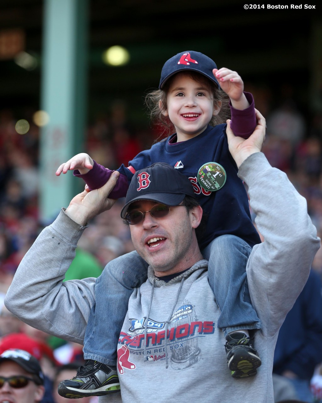 """A father holds his daughter up as they cheer during a game between the Boston Red Sox and the Baltimore Orioles Saturday, April 19, 2014 at Fenway Park in Boston, Massachusetts."""