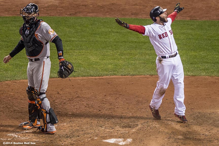 """Boston Red Sox second baseman Dustin Pedroia reacts after scoring the winning run on a throwing error in the ninth inning of a game against the Baltimore Orioles at Fenway Park Sunday, April 20, 2014. The Red Sox won 6-5."""
