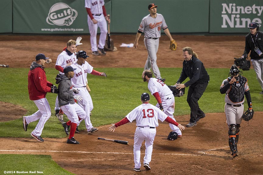 """Members of the Boston Red Sox celebrate after second baseman Dustin Pedroia scored the winning run on a throwing error in the ninth inning of a game against the Baltimore Orioles at Fenway Park Sunday, April 20, 2014. The Red Sox won 6-5."""