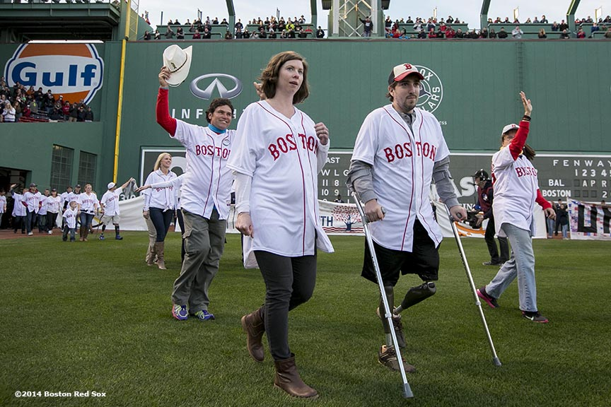 """Boston Marathon survivor Jeff Bauman and rescuer Carlos Arredondo are introduced during a ceremony recognizing the Boston Marathon bombings before a game between the Boston Red Sox and the Baltimore Orioles Sunday, April 20, 2014 at Fenway Park in Boston, Massachusetts."""