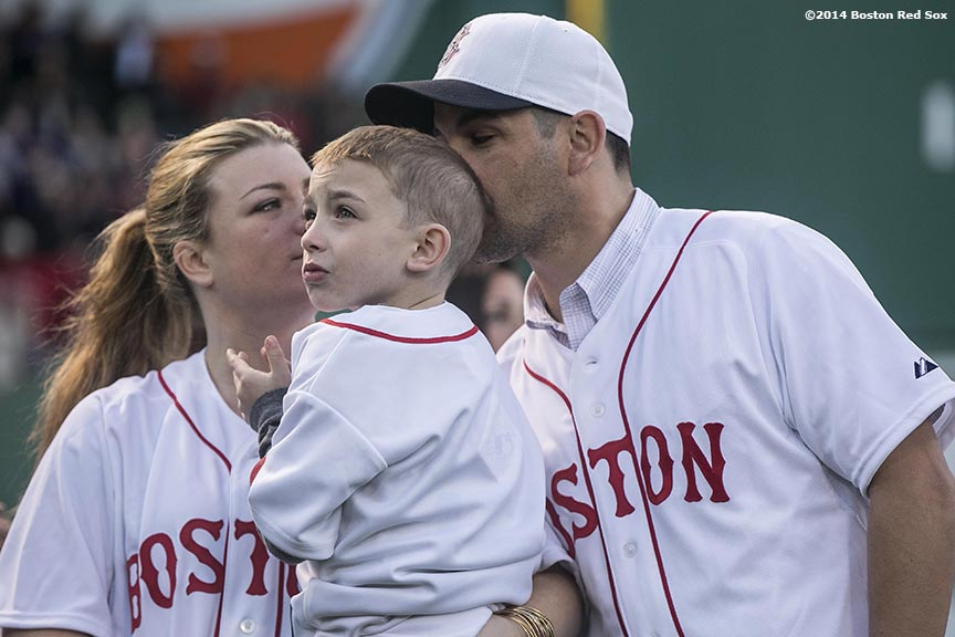 """Boston Marathon bombing survivor Marc Fucarile kisses his son Gavin alongside his wife, Jen Regan, as they are introduced during a ceremony recognizing the Boston Marathon bombings before a game between the Boston Red Sox and the Baltimore Orioles Sunday, April 20, 2014 at Fenway Park in Boston, Massachusetts."""