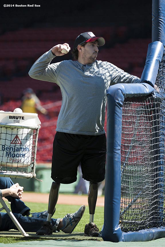 """Boston Marathon bombing survivor Jeff Bauman throws batting practice to Boston Red Sox catcher David Ross and outfielder Jonny Gomes at Fenway Park in Boston, Massachusetts Sunday, April 20, 2014."""