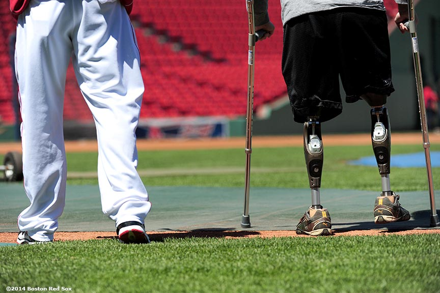 """Boston Marathon bombing survivor Jeff Bauman walks alongside Boston Red Sox outfielder Jonny Gomes before throwing batting practice to Gomes and Boston Red Sox catcher David Ross at Fenway Park in Boston, Massachusetts Sunday, April 20, 2014."""