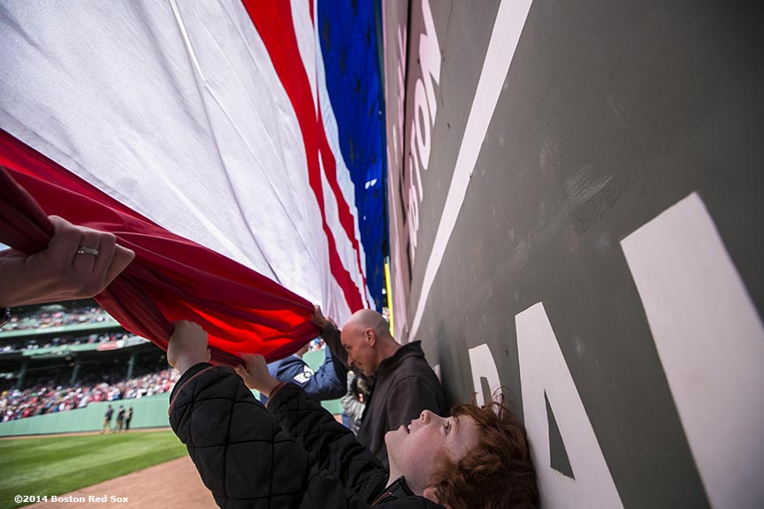 """A boy holds an American flag as it is unfurled over the Green Monster during a pre-game ceremony before a game between the Baltimore Orioles and the Boston Red Sox at Fenway Park in Boston, Massachusetts Monday, April 21, 2014."""