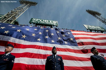 """Members of the Hanscom Air Force base stand as an American flag is unfurled over the Green Monster during a pre-game ceremony before a game between the Baltimore Orioles and the Boston Red Sox. """