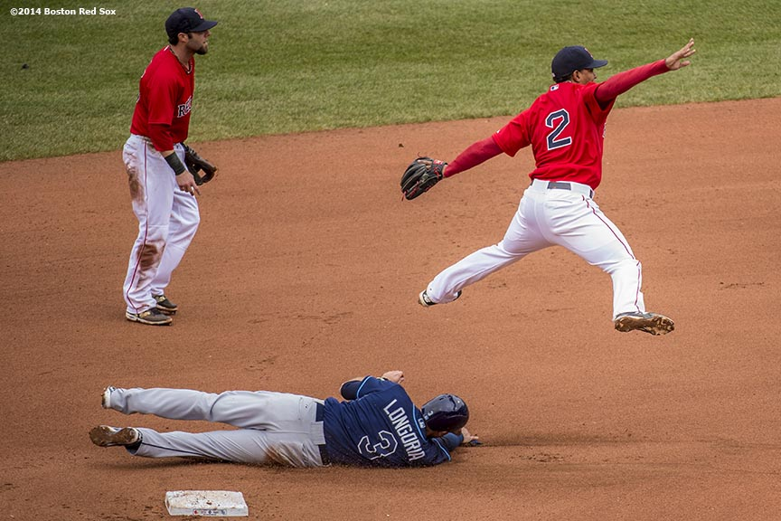 """Boston Red Sox shortstop Xander Bogaerts leaps as he turns a double play over third baseman Evan Longoria during the sixth inning of the first game of a day-night double header against the Tampa Bay Rays Thursday, May 1, 2014 at Fenway Park in Boston, Massachusetts."""