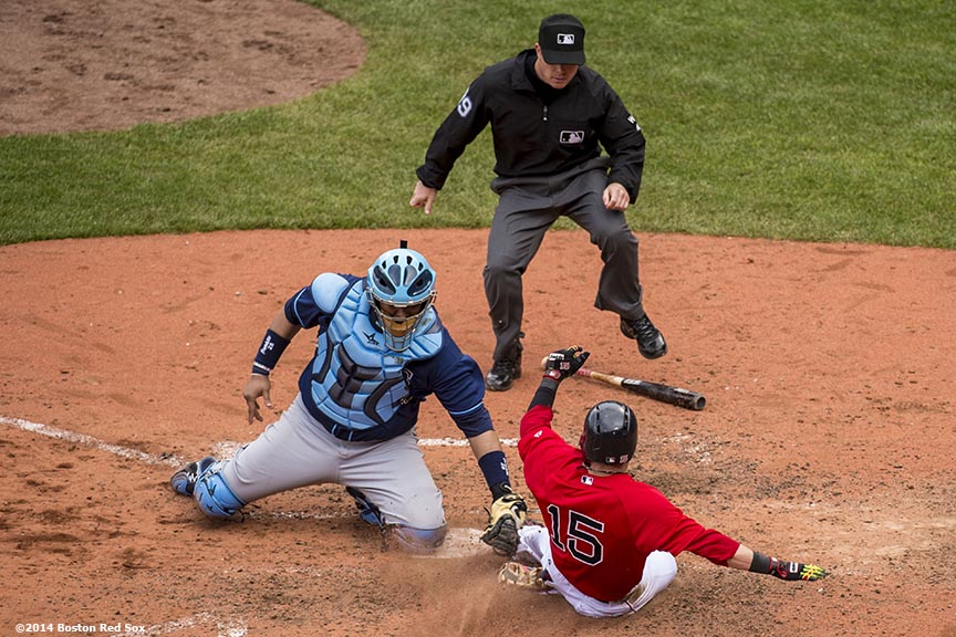 """Boston Red Sox second baseman Dustin Pedroia slides into home plate but is tagged out by catcher José Molina after a double by designated hitter David Ortiz during the seventh inning of the first game of a day-night double header against the Tampa Bay Rays Thursday, May 1, 2014 at Fenway Park in Boston, Massachusetts. The controversial call stood after being reviewed."""