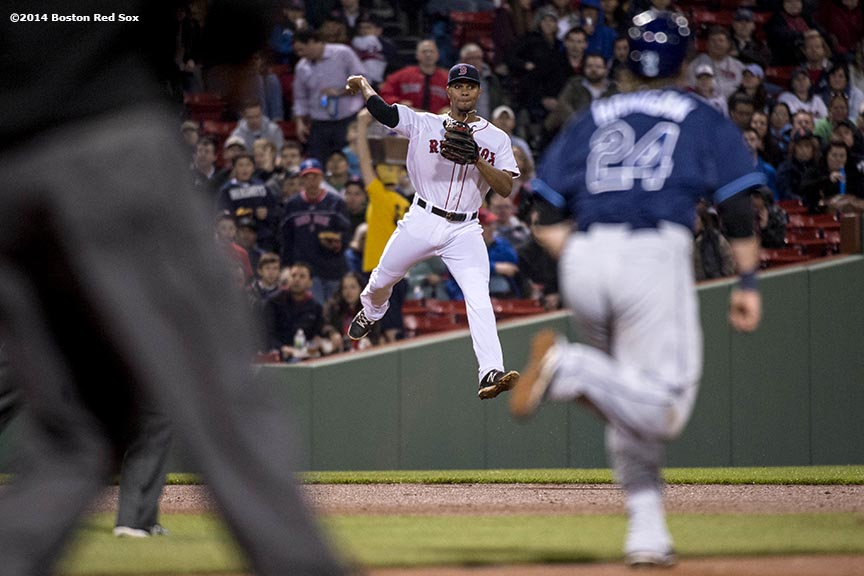 """Boston Red Sox shortstop Xander Bogaerts leaps as he throws to second base during the fourth inning of the second game of a day-night double header against the Tampa Bay Rays Thursday, May 2, 2014 at Fenway Park in Boston, Massachusetts."""